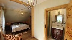 Pokój z łożem małżeńskim i łazienką na piętrze.